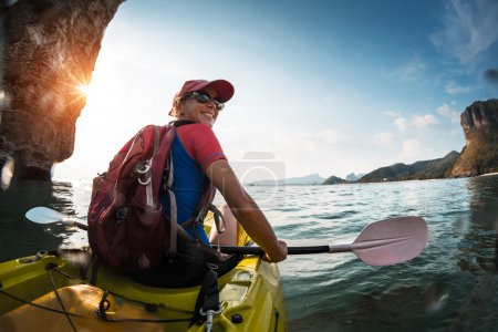 Photo for Woman paddling the sea kayak in the tropical calm lagoon with mountains - Royalty Free Image