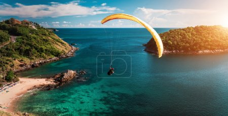 Photo for Skydiver flying over the water during sunset with the mountains - Royalty Free Image