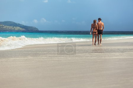 Young couple walking on sandy beach
