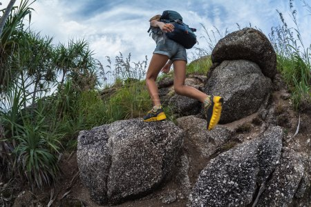 Lady hiker passing rocky terrain