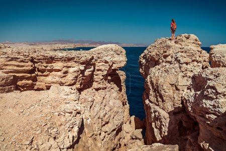 girl standing on the top of the cliff