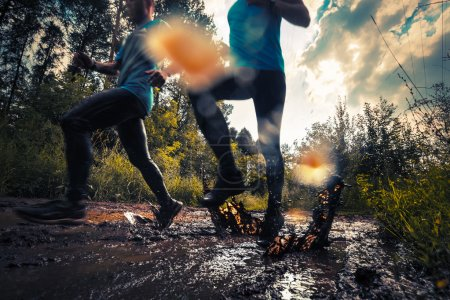 Two athletes running through the dirty puddle