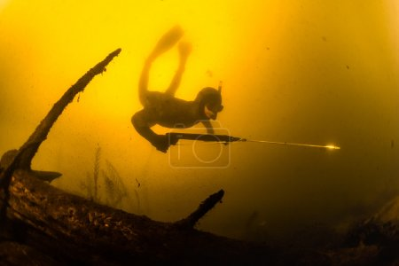 hunter with speargun in a lake