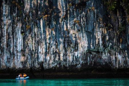 People on boat near huge limestone rock