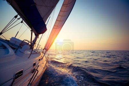 Photo pour Voilier glisse en pleine mer au coucher du soleil - image libre de droit