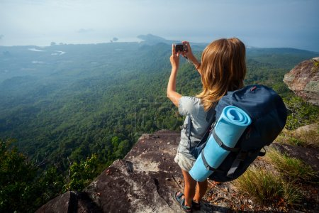Photo for Female hiker taking picture of the valley from top of the hill - Royalty Free Image