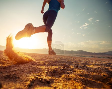 Photo for Young lady running in the desert at sunset - Royalty Free Image