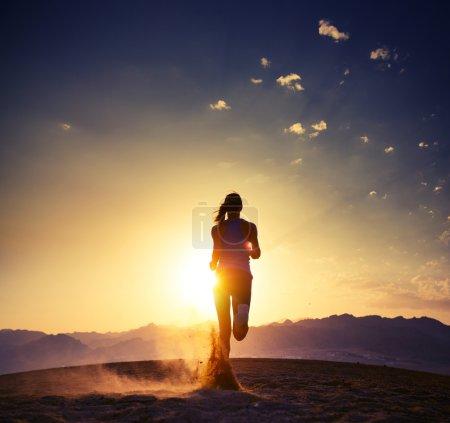 Photo pour Jeune femme courant dans le désert au coucher du soleil - image libre de droit