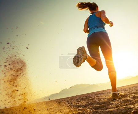 Photo for Young lady running in a desert at sunset - Royalty Free Image