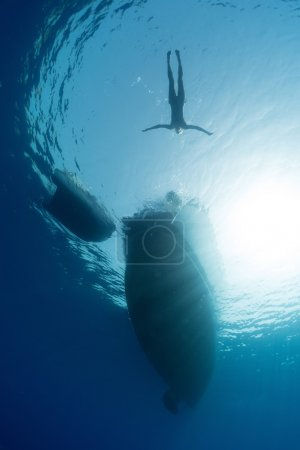 Photo pour Underwater view of the woman swimming around the sail boat in tropical clear sea - image libre de droit