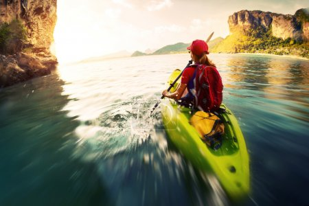 Photo for Young lady paddling the kayak in a bay with limestone mountains. Motion blurred water surface - Royalty Free Image