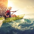 Young lady paddling hard the kayak with lots of sp...