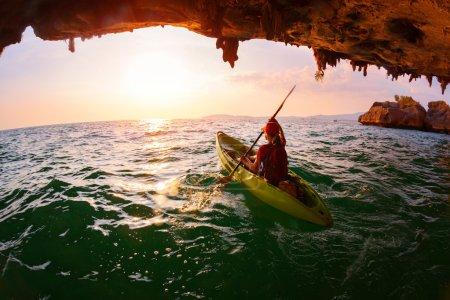 Photo pour Jeune femme pagayant le kayak de la grotte de calcaire vers la mer ouverte - image libre de droit