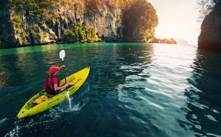 Photo for Young lady paddling the kayak in the calm bay with limestone mountains - Royalty Free Image
