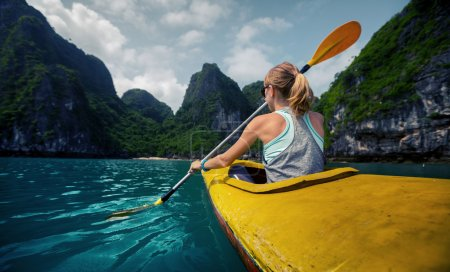 Photo pour Femme explorant calme baie tropicale avec des montagnes de calcaire en kayak. Ha Long Bay, Vietnam - image libre de droit