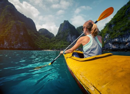 Photo for Woman exploring calm tropical bay with limestone mountains by kayak. Ha Long Bay, Vietnam - Royalty Free Image