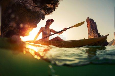 Young lady paddling the kayak