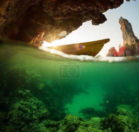 Photo pour Kayak de pagaie dame dans la mer tropicale près de la roche avec vue sous-marine sur le récif corallien - image libre de droit