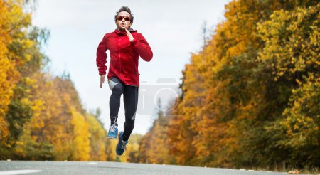 Photo for Young athlete running on the autumn road - Royalty Free Image