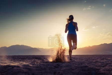 Photo for Lady running in the desert at sunset - Royalty Free Image