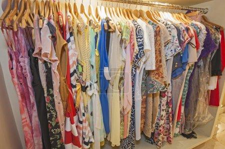 Photo pour Variété de vêtements de mode d'été colorés pour femmes suspendus sur rail dans un magasin de détail - image libre de droit