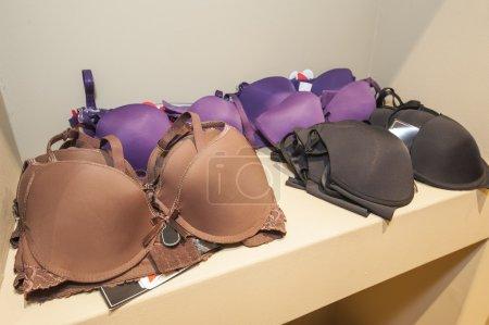 Photo pour Présentoir de soutien-gorge lingerie femme vêtements sur étagère en bois dans la boutique de vêtements - image libre de droit