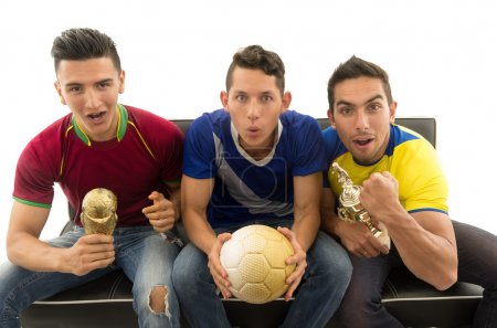 Three friends sitting on sofa wearing sports shirts, holding ball and trophy screaming cheering at camera with enthusiasm, white background, shot from above