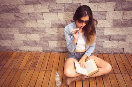 Young hip brunette sitting legs crossed on wooden surface leaning back towards stone wall, smoking e-cigarette happily and reading book