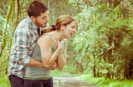 Foto de Asfixia con hombre de pie detrás de realizar maniobra de heimlich, ambiente del parque y ropa casual de mujer joven. - Imagen libre de derechos