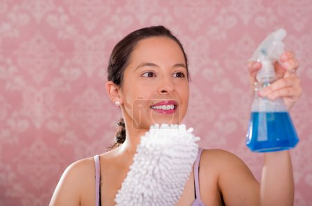 Brunette woman holding spray bottle of blue liquid and white fluffy cleaning brush while smiling to camera, pink background