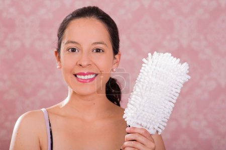 Brunette woman holding white fluffy cleaning brush while smiling to camera, pink background