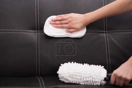 White fabric brush from steam cleaning machine being used on black leather couch, hand rubbing sofa with cloth