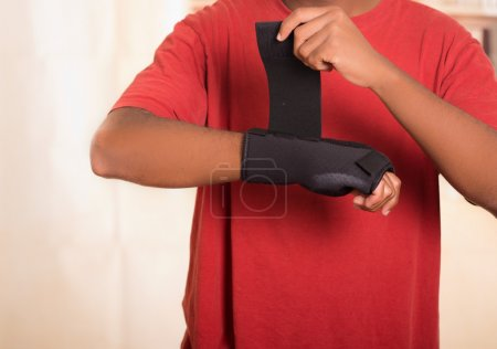 Closeup man in red shirt wearing black wrist brace support on right hand, tightening velcro using other arm