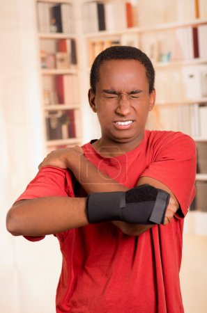 Man in red shirt wearing wrist brace support on right hand posing for camera, holding his shoulder with other arm simulating painful movements