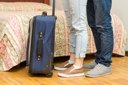 Closeup legs of couple wearing jeans, standing next to bed, blue suitcase on floor, hostel concept
