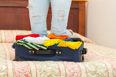 Open suitcase with clothes inside lying on bed, womans legs in background, hostel guest concept
