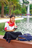 Young woman wearing traditional andean skirt and blouse with matching red necklace, sitting on bench next to lake in park area, relaxing while using tablet, smiling happily