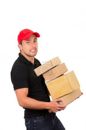 Photo for Happy friendly confident delivery man carrying boxesside view isolated on white - Royalty Free Image
