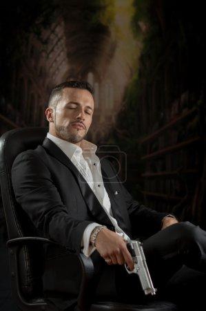 Foto de Elegante guapo latino gangster mafia espía sicario asesino mirando hacia abajo sentado en una silla sosteniendo un arma sobre fondo oscuro - Imagen libre de derechos