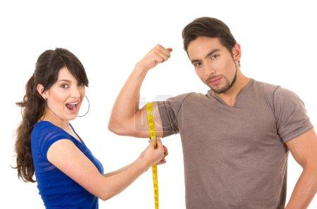 beautiful girl holding measuing tape around handsome muscular man