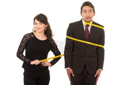 Photo pour Jeune belle femme tailleur couturier liens confus homme autour avec ruban à mesurer isolé sur blanc - image libre de droit