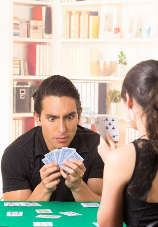 young couple playing cards cuarenta