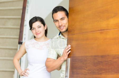 happy attractive couple opening the door to their new house