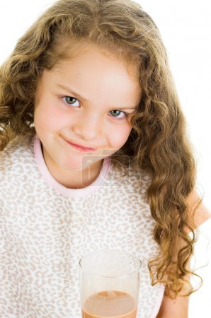 Cute little preschooler girl holding a glass of chocolate milk