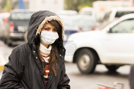 young girl walking wearing jacket and a mask in the city street concept of  pollution
