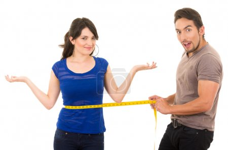 handsome man holding measuring tape around thin young girl