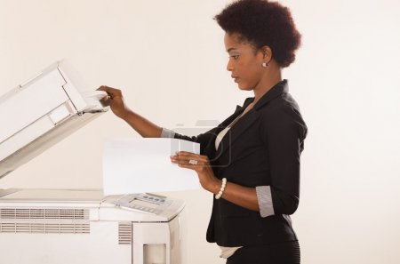 Photo for Black office woman lifting up lid of copy machine and holds a paper in other hand - Royalty Free Image