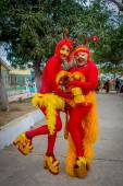 Two joyful girls dressed as chapulin colorado and high heels  participate in Colombias most important folklore celebration, the Carnival of Barranquilla, Colombia