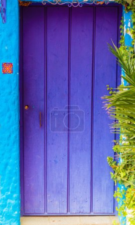 Caption of purple wooden door on turquoise painted house
