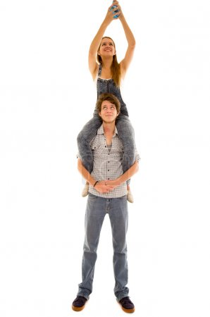Woman sitting on mans shoulders while she assembles a blue lightbulb high up and he looks upwards smiling carefully